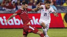 David Edgar (left) of Canada battles for the ball against David Ramirez of Costa Rica during the CONCACAF Gold Cup soccer action in Toronto on July 14, 2015. (Aaron Vincent Elkaim/THE CANADIAN PRESS)