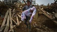 Mao Changxue carries the body of his son after it was dug out from the debris of their home, which collapsed when a magnitude 6.3 earthquake hit Longtoushan town, Ludian county of Zhaotong, Yunnan province, August 4, 2014. (CHINA STRINGER NETWORK/REUTERS)