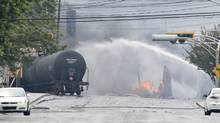 Smoke and fire rise from railway cars that were carrying crude oil after derailing in downtown Lac-Megantic, Que., on July 6, 2013. (Paul Chiasson/The Canadian Press)