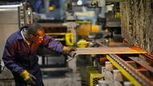 A worker fires steel stuts at Standen's Ltd. in Calgary. (Chris Bolin For The Globe and Mail)