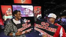 Atlanta Falcons fans Stephen Hamilton, left, and George Arnold gather all the Falcons swag they can, at the NFL Experience on Thursday, Feb. 2, 2017, in Houston. The Falcons face the New England Patriots on Sunday in the NFL football Super Bowl. (Curtis Compton/AP)