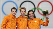 Athletes from the Netherlands, from left to right, silver medalist Sven Kramer, gold medalist Jorrit Bergsma, and bronze medalist Bob de Jong stand on the podium during the flower ceremony for the men's 10,000-meter speed skating race at the Adler Arena Skating Center during the 2014 Winter Olympics in Sochi, Russia, Tuesday, Feb. 18, 2014. (Patrick Semansky/AP)