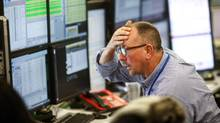 A trader reacts as he looks at financial data on computer screens on the trading floor at ETX Capital, a broker of contracts-for-difference in London, U.K., on Wednesday, Nov. 9. (Chris Ratcliffe/Bloomberg)