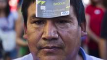 "A protester, with a fake Bankia bank credit card on his forehead, takes part in a demonstration against bank fraud in Madrid June 16, 2012. The card reads ""Bronca"" (Quarrel) instead of ""Bankia,"" ""Risa"" (Laugh) instead of Visa and it bears the name of former chairman of Spain's Bankia bank Rodrigo Rato. (SUSANA VERA/REUTERS)"