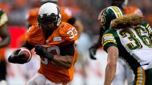 B.C. Lions' Andrew Harris, left, rushes for a first down as Edmonton Eskimos' Aaron Grymes moves in for the tackle during the first half of a CFL game in Vancouver, B.C., on Saturday July 20, 2013. (DARRYL DYCK/THE CANADIAN PRESS)
