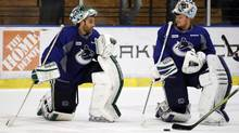 Vancouver Canucks goaltenders Roberto Luongo (L) and Cory Schneider (R) talk on the ice during practice for Game 4 of their NHL Western Conference quarter-final playoff against the Los Angeles Kings at the Kings' practice facility in El Segundo, California April 17, 2012. (DANNY MOLOSHOK/REUTERS)