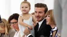 Former England soccer captain David Beckham holds his daughter, Harper, as he speaks to Vogue editor Anna Wintour while waiting for a presentation of the Victoria Beckham Spring/Summer 2014 collection during New York Fashion Week, Sept. 8, 2013. (LUCAS JACKSON/REUTERS)