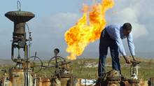 A worker turning a valve at the Shirawa oil field. No companies submitted bids to work on the Baghdad East oil field or the cluster of fields known as Eastern Fields as part of an Iraqi auction of its energy resources on December 11, 2009, Oil Minister Hussein al-Shahristani said. Meanwhile, Iraq reached agreement with energy giants Shell and Petronas for the massive Majnoon southern oil field. (KARIM SAHIB)