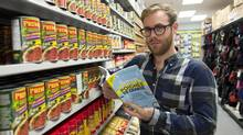 Jonathan Lemieux, author of Survivre avec une poignee de change (Surviving on a Handfull of Change), poses at a Dollar store in Montreal, Saturday, September 28, 2013. (Graham Hughes/THE CANADIAN PRESS)