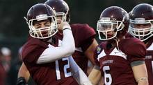 McMaster University Marauders quarterback Kyle Quinlan, 12, celebrates with teammate after scoring a touchdown against University of Calgary Dinos during first half Mitchell Bowl football action in Hamilton, Ontario, on Saturday, Nov. 17, 2012. (Dave Chidley/THE CANADIAN PRESS)