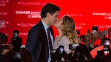 Justin Trudeau kisses his wife Sophie as they arrive on stage in Montreal on Oct. 20. (NICHOLAS KAMM/AFP/Getty Images)