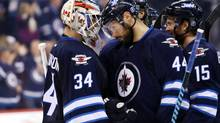 Winnipeg Jets goalie Michael Hutchinson (34) celebrates his teams win over the New Jersey Devils with teammate defenceman Zach Bogosian (44) during the third period at MTS Centre. Winnipeg won 3-1. (Bruce Fedyck/USA TODAY Sports)
