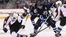 Nathan MacKinnon #29 of the Colorado Avalanche gets tripped up as he fights for the puck with Blake Wheeler #26 of the Winnipeg Jets in second period action in an NHL game at the MTS Centre on January 18, 2016 in Winnipeg, Manitoba, Canada. (Marianne Helm/Getty Images)