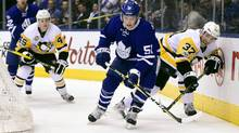 Toronto Maple Leafs defenceman Jake Gardiner and Pittsburgh Penguins right wing Carter Rowney vie for control of the puck during first period NHL hockey action, in Toronto on Saturday, April 8, 2017. (Frank Gunn/THE CANADIAN PRESS)