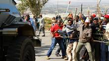 Striking miners react as they make way for a security vehicle at the AngloGold Ashanti mine in Carletonville, northwest of Johannesburg, Oct. 25, 2012. AngloGold Ashanti sacked 12,000 wildcat strikers who defied a deadline to return to work on Wednesday. (SIPHIWE SIBEKO/REUTERS)