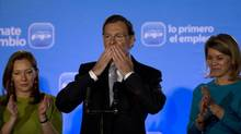Prime-minister-designate Mariano Rajoy greets supporters after winning Spain's national election on Sunday, Nov. 20, 2011. He is accompanied by his wife, Elvira Fernandez Balboa, left, and Maria Dolores de Cospedal, secretary-general of the Popular Party. (Emilio Morenatti/Emilio Morenatti/AP)