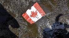 A placard with the Canadian flag rests on the ground covered in oil as demonstrators conduct a die-in to protest against the Keystone Pipeline and the Alberta Tar Sands outside of the Canadian Consulate in downtown Chicago, Thursday, May 17, 2012. (Nam Y. Huh/AP)