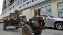 A farmer drives a tractor past a branch of Agricultural Bank of China in Xiangfan, Hubei province July 1, 2010. Agricultural Bank of China's Hong Kong share offering has been more than 10 times oversubscribed by institutional investors, signalling healthy interest in the dual listing that could end up being the world's largest ever. REUTERS/Stringer (CHINA - Tags: BUSINESS) CHINA OUT. NO COMMERCIAL OR EDITORIAL SALES IN CHINA (� Stringer Shanghai / Reuters/� Stringer Shanghai / Reuters/R)
