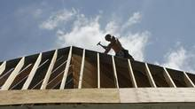 A worker constructs a new home in Geneva, Ill. in this file photo. (JEFF HAYNES/REUTERS)