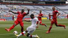 Canada's Ashtone Morgan, foreground, tries to shoot the ball while covered by, from back left, Panama's Harold Cummings, Jairo Jimenez and Roberto Chen in the first half of a CONCACAF Gold Cup soccer match on Sunday, July 14, 2013, in Denver. (David Zalubowski/AP)