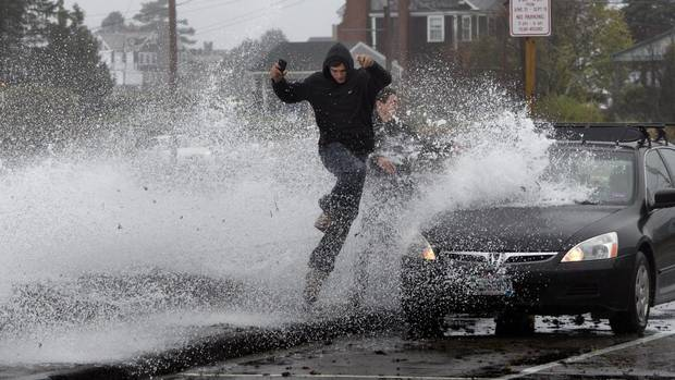 Caleb Lavoie, 17, of Dayton, Maine, front, and Curtis Huard, 16, of Arundel, Maine, leap out of the way as a large wave crashes over a seawall on the Atlantic Ocean during the early stages of Superstorm Sandy, Monday, Oct. 29, 2012, in Kennebunk, Maine. (Robert F. Bukaty/AP)