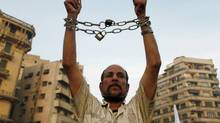 An anti-Morsi protester in Tahrir Square uses chains to symbolize Muslim Brotherhood rule. (ASMAA WAGUIH/REUTERS)