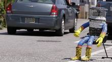 In this July 17, 2015, file photo, a car drives by HitchBOT, a hitchhiking robot in Marblehead, Mass. The Canadian researchers who created hitchBOT as a social experiment say someone in Philadelphia damaged the robot beyond repair on Saturday, Aug. 1, ending its brief American tour. The robot was trying to travel cross-country after successfully hitchhiking across Canada last year and parts of Europe. (Stephan Savoia/AP)