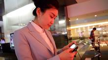A staff member inspects a cellphone at Samsung's main showroom in Seoul. (Sean Gallagher For The Globe and Mail)