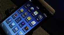 A man holds the new touchscreen BlackBerry Z10 smartphone, during a launch event for the new phone in London, on Jan. 30, 2013. (Lefteris Pitarakis/AP)