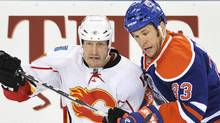 Calgary Flames' Tim Jackman (L) and Edmonton Oilers' Steve MacIntyre tangle during the first period of their NHL hockey game in Edmonton March 26, 2011. REUTERS/Dan Riedlhuber (DAN RIEDLHUBER)