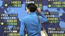 A man checks global stock index in Tokyo (Koji Sasahara/AP)