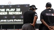Umpire Joe West (22) connects with MLB's review command center in New York to review an attempted sliding catch of a foul ball, May 16, 2015. (Brandon Wade/ASSOCIATED PRESS)