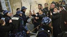 Palestinian police officers intervene in a fight between Greek Orthodox and Armenian clergymen during the cleaning of the Church of the Nativity in Bethlehem on Dec. 28, 2011. (Bernat Armangue/Bernat Armangue/AP)