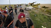 Pro-Russian separatists stand guard at the crash site of Malaysia Airlines Flight MH17, near the village of Hrabove, Donetsk region, July 20, 2014. (MAXIM ZMEYEV/REUTERS)