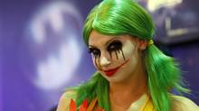 "A woman dressed as the character ""The Joker"" smiles for the camera while promoting Warner Bros. Interactive Entertainment, Inc.'s new video game ""Gotham City Impostors"" during the Electronic Entertainment Expo or E3 in Los Angeles June 8, 2011. (DANNY MOLOSHOK/DANNY MOLOSHOK / Reuters)"