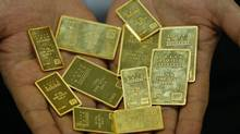 An employee at the Korea Gold Exchange shows off gold bars in Seoul, South Korea, Tuesday, Aug. 9, 2011. (Lee Jin-man/AP)