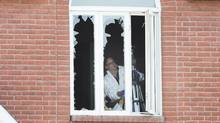 A crime scene investigator surveys the inside of a home in Boucherville, Que., on Friday, July 1, 2015, where the bodies of three men were found. (Graham Hughes/THE CANADIAN PRESS)