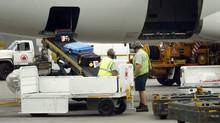 Baggage handlers unload an Air Canada flight at Toronto Pearson International Airport. (Fred Lum/Fred Lum/The Globe and Mail)