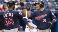 Minnesota Twins Brian Dozier (2) celebrates his two-run home run with teammate Danny Santana (39) while playing against the Toronto Blue Jays during first inning AL baseball action in Toronto on Tuesday, June 10, 2014. (Nathan Denette/THE CANADIAN PRESS)