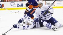 Toronto Maple Leafs forward Nazem Kadri tries to control the puck after colliding with defenceman Carl Gunnarsson against the New York Islanders. (John E. Sokolowski/US PRESSWIRE/John E. Sokolowski/US PRESSWIRE)