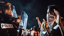 Police officers face off with people protesting the shooting death of Keith Lamont Scott on Sept. 21, 2016, in Charlotte, N.C. (Sean Rayford)