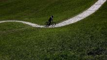 A cyclist makes his way through the Olympic park in Munich, Germany, Wednesday, April 25, 2012. Sunny weather is forecasted for Germany during the next few days. (AP Photo/Matthias Schrader) (Matthias Schrader/Matthias Schrader/AP)