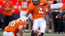 B.C. Lions' Paul McCallum, right, kicks a field goal during a game in 2013. (Darryl Dyck/The Canadian Press)