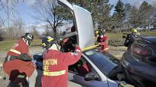 Burlington firefighters use saws and the jaws of life to remove a car roof. (J.P. MOCZULSKI For The Globe and Mail)
