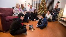 The Papazian family, seen in their family home in Burnaby on Dec. 13, sitting to the left of the Christmas tree, sponsored the Cholakian family, seen right foreground, to come to Canada from Syria. (Ben Nelms/The Globe and Mail)