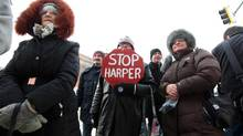 "Mary Hutchings holds a ""Stop Harper"" placard while gathering with veterans and supporters outside the Veterans Affairs Office in Brandon, Man., on Jan. 31, 2014. (TIM SMITH/THE CANADIAN PRESS)"
