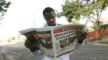 A Kenyan man reads a newspaper a day after the country's presidential election, at a roadside stall in Nairobi, March 5, 2013. (Sayyid Azim/AP)