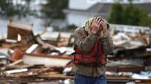 Brian Hajeski, 41, of Brick, N.J., reacts after looking at debris of a home that washed up on to the Mantoloking Bridge the morning after superstorm Sandy rolled through, Tuesday, Oct. 30, 2012, in Mantoloking, N.J. (Julio Cortez/AP Photo)
