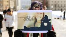 Mervin Leclair holds up a photo of Loretta Saunders during a vigil in Ottawa on March 5, 2014. Victoria Henneberry, 28, and her boyfriend, Blake Leggette, 26, are charged with first-degree murder in connection with Ms. Saunders's death. (DAVE CHAN FOR THE GLOBE AND MAIL)