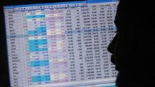 A broker monitors a computer screen displaying stock information while sitting inside a booth at Karachi Stock Exchange. (Akhtar Soomroo/Reuters)